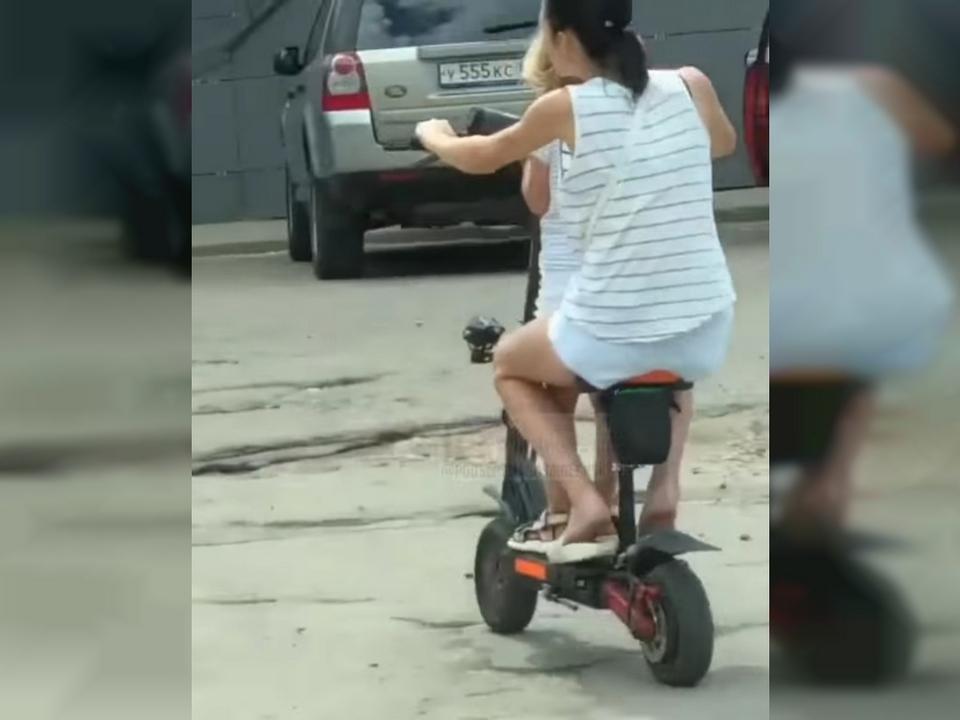 женщина с ребёнком на электросамокате, улица 25 Сентября (кадр видео )
